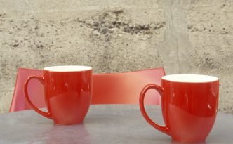 Two red cups on stainless steel table